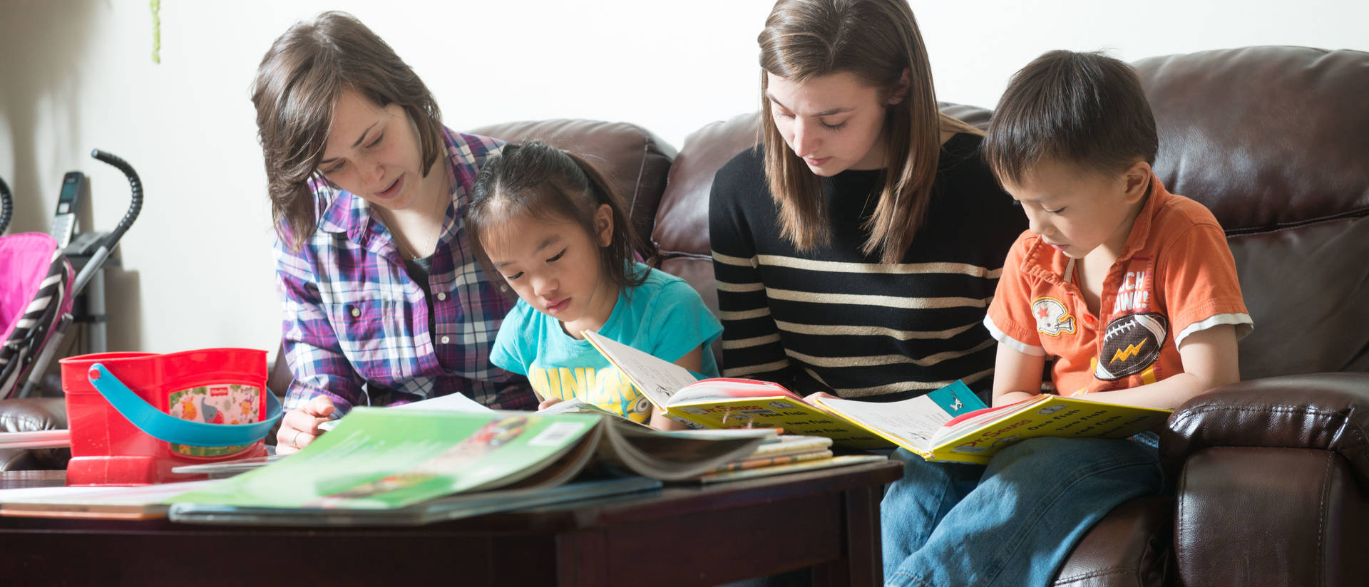 Students in a home with young kids for reading partners
