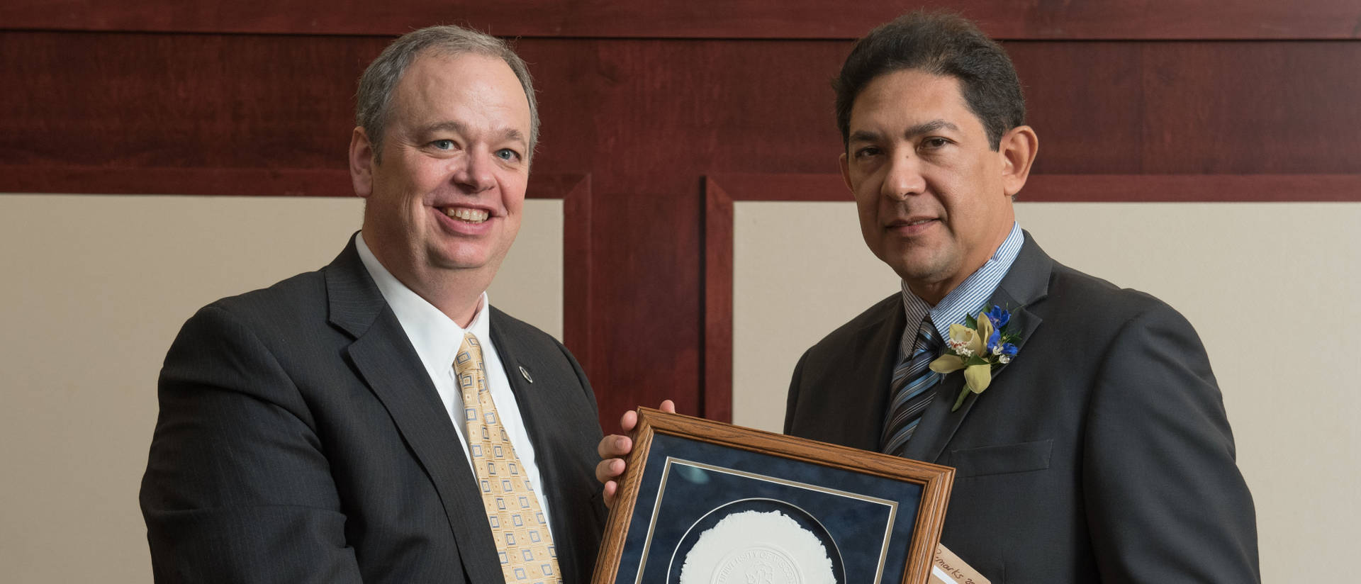 Chancellor Jim hands Alumni Award to recipient.