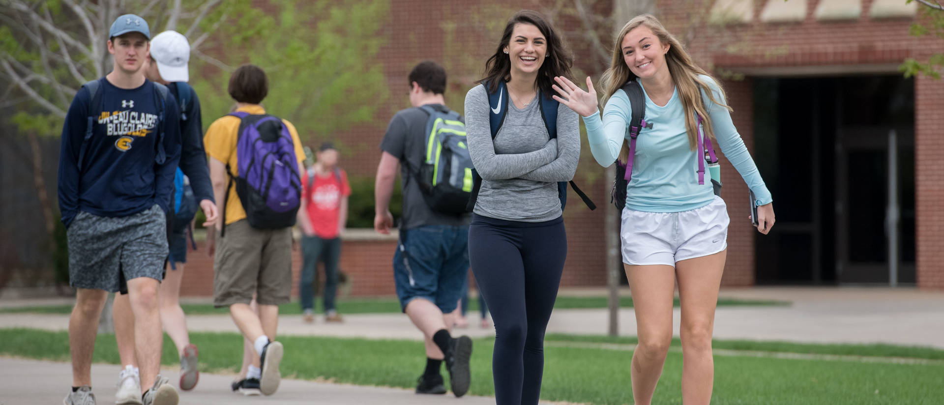 female student waving at the camera on campus mall
