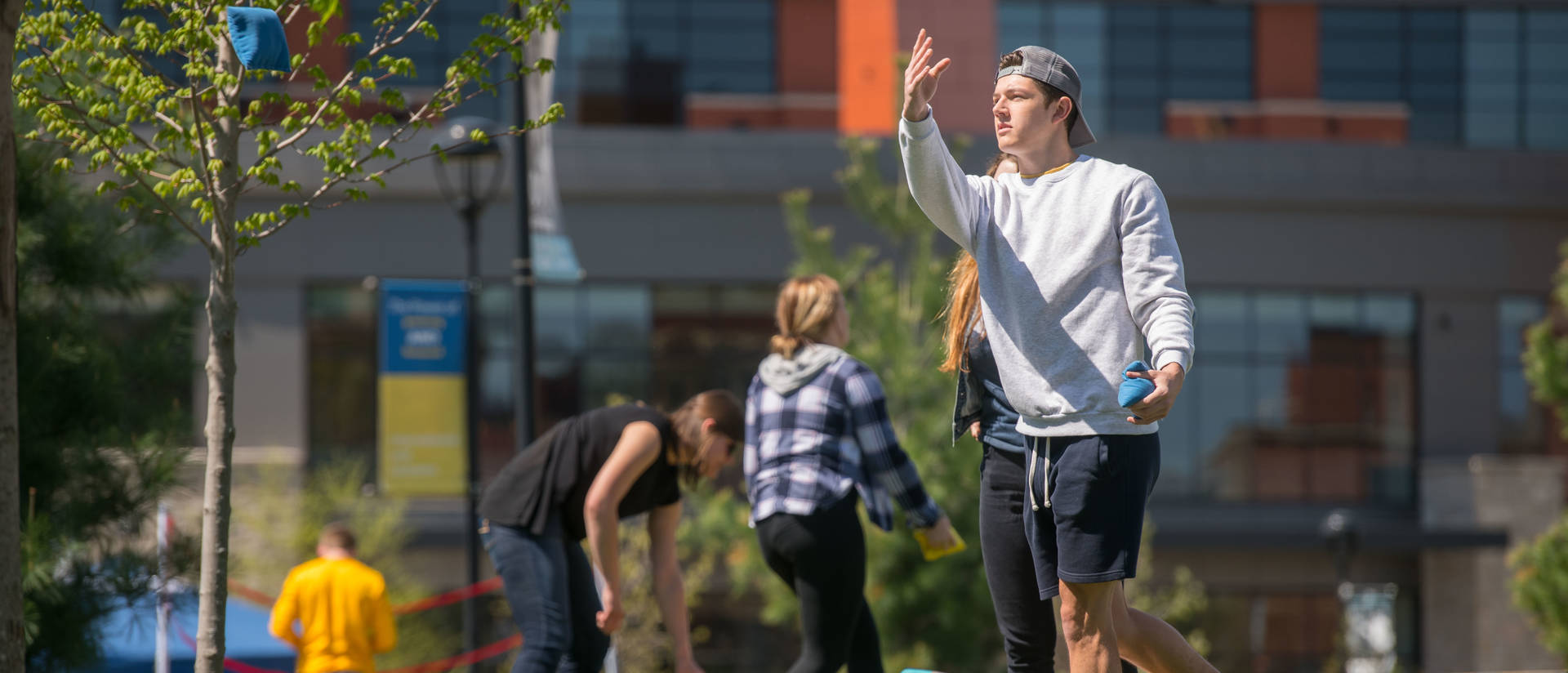 Male student tossing bags for bean bag game on campus mall, spring