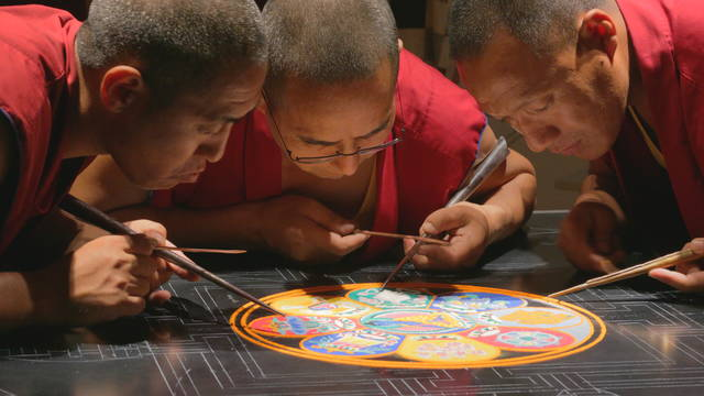 Tibetan monks creating sand paint mandala