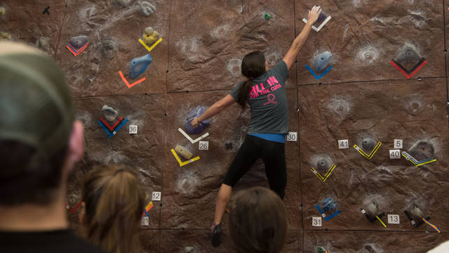 Female student climbing rock wall