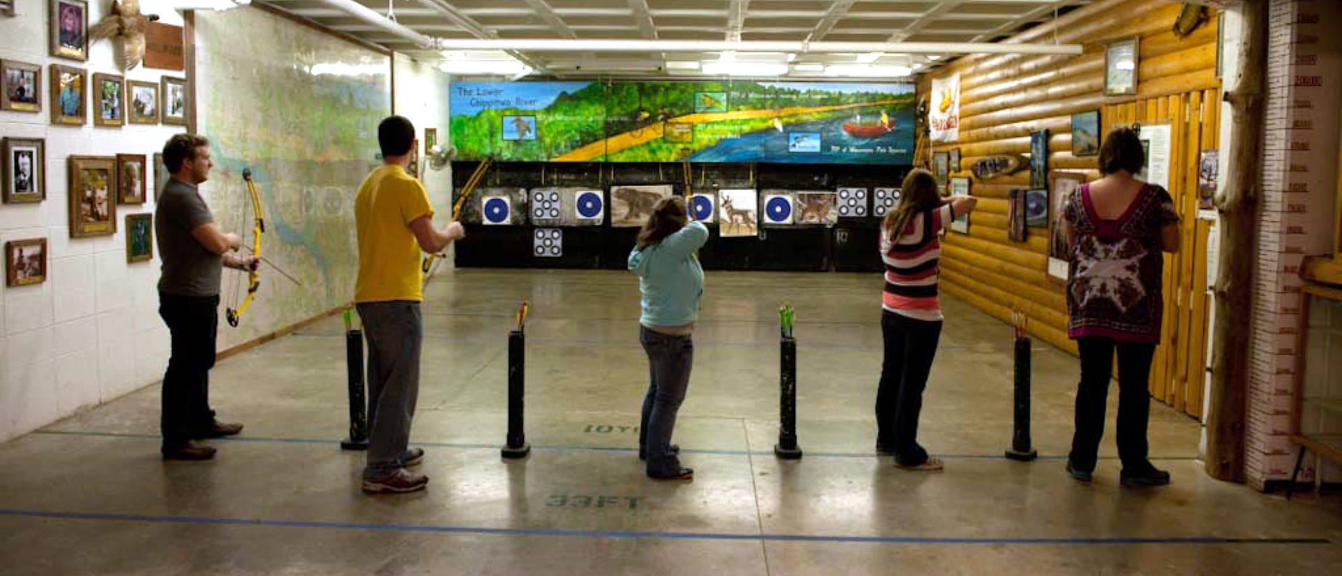 Five students lined up in archery range