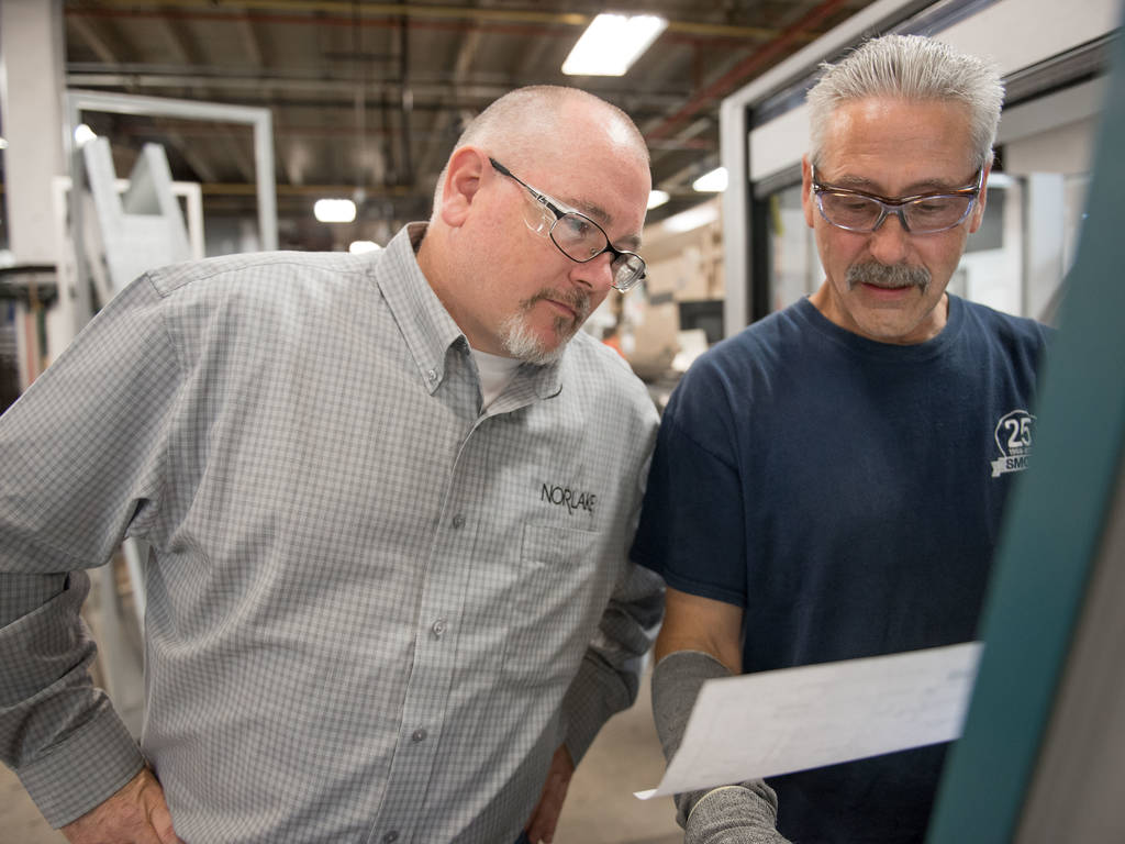 Manager talking with employee in factory setting