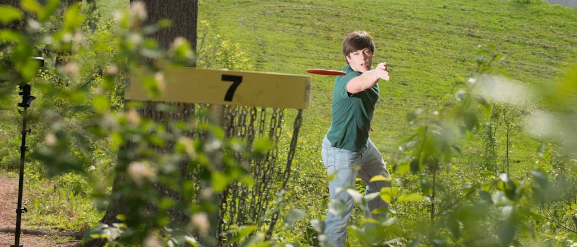 Student playing disc golf