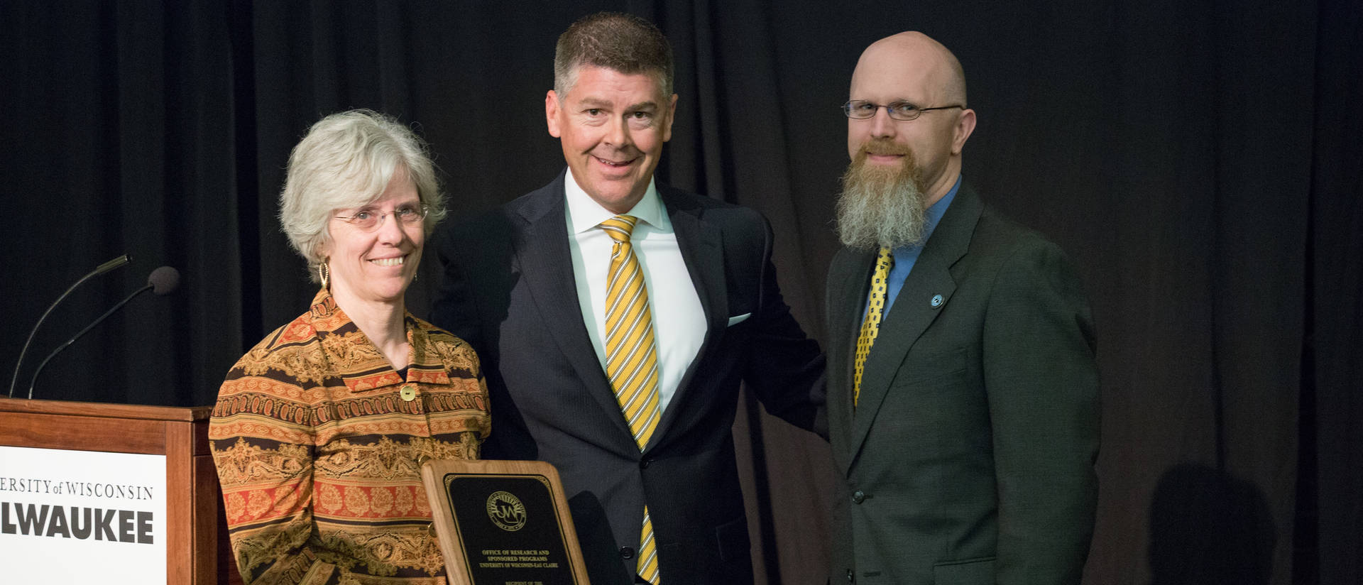 UW-Eau Claire's Karen Havholm, Assistant Vice Chancellor (left), and Director of Grants and Contracts, Jeremy Miner (right), with Regent Director Drew Peterson (middle)