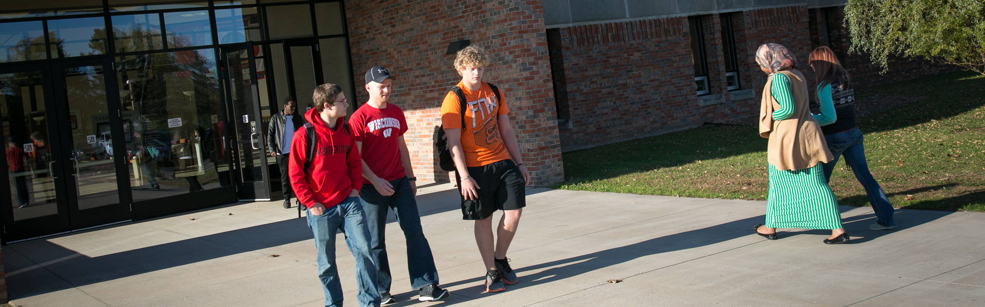 Student walking in an dout of Commons building, Rice Lake