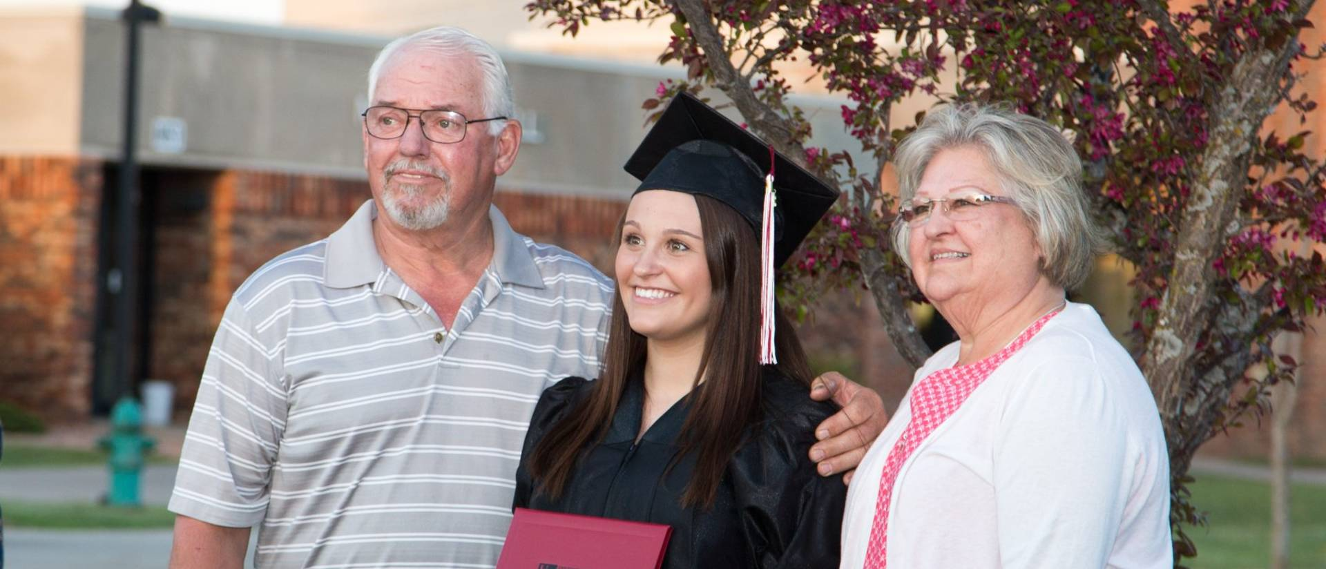 Barron County graduate with her parents at commencement