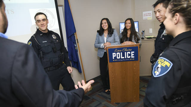 Police officers talk with UW-Eau Claire student researchers about their study on the health benefits of carrying equipment on vests instead of belts.