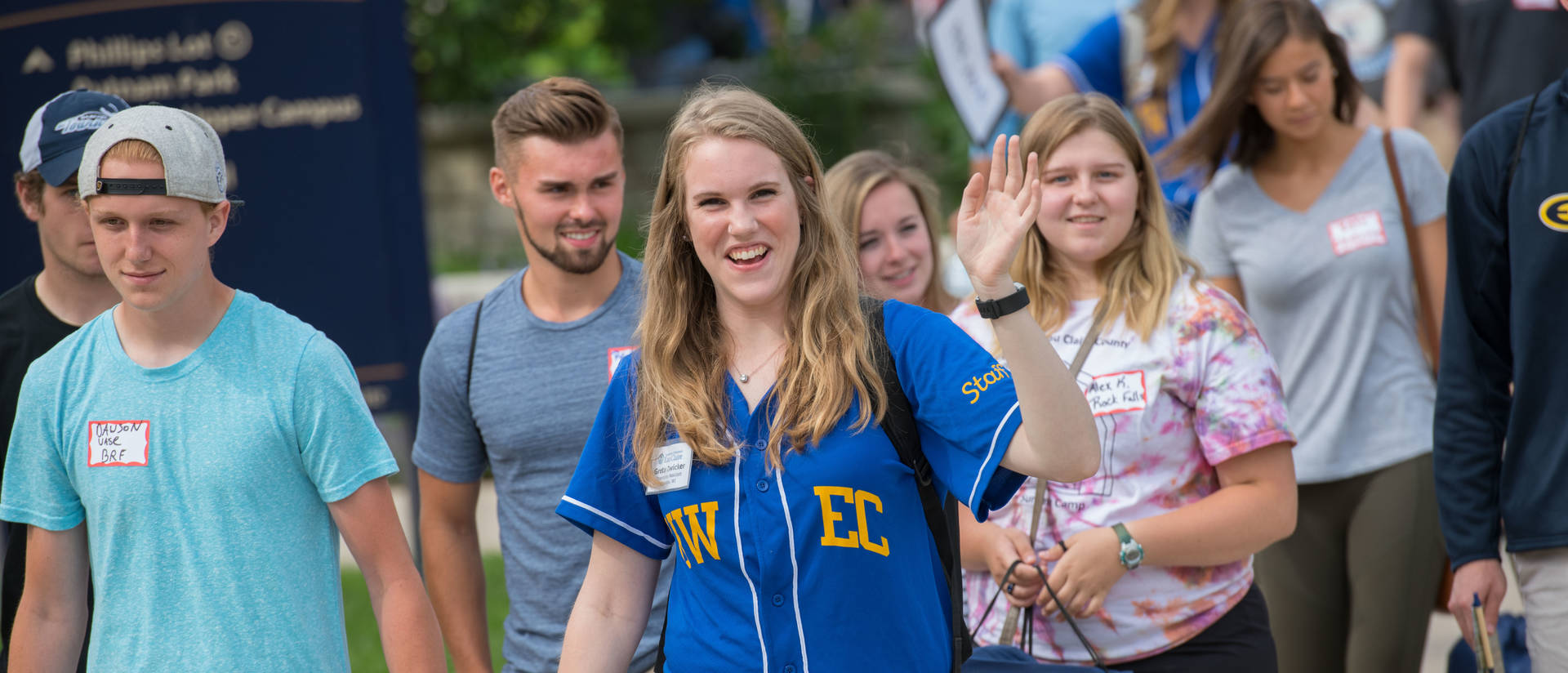 Orientation leader in a blue uwec t-shirt walking with new students