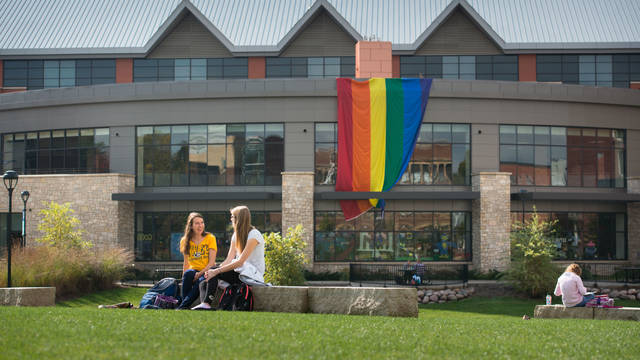 UWEC students study in campus mall in front of PRIDE flag.