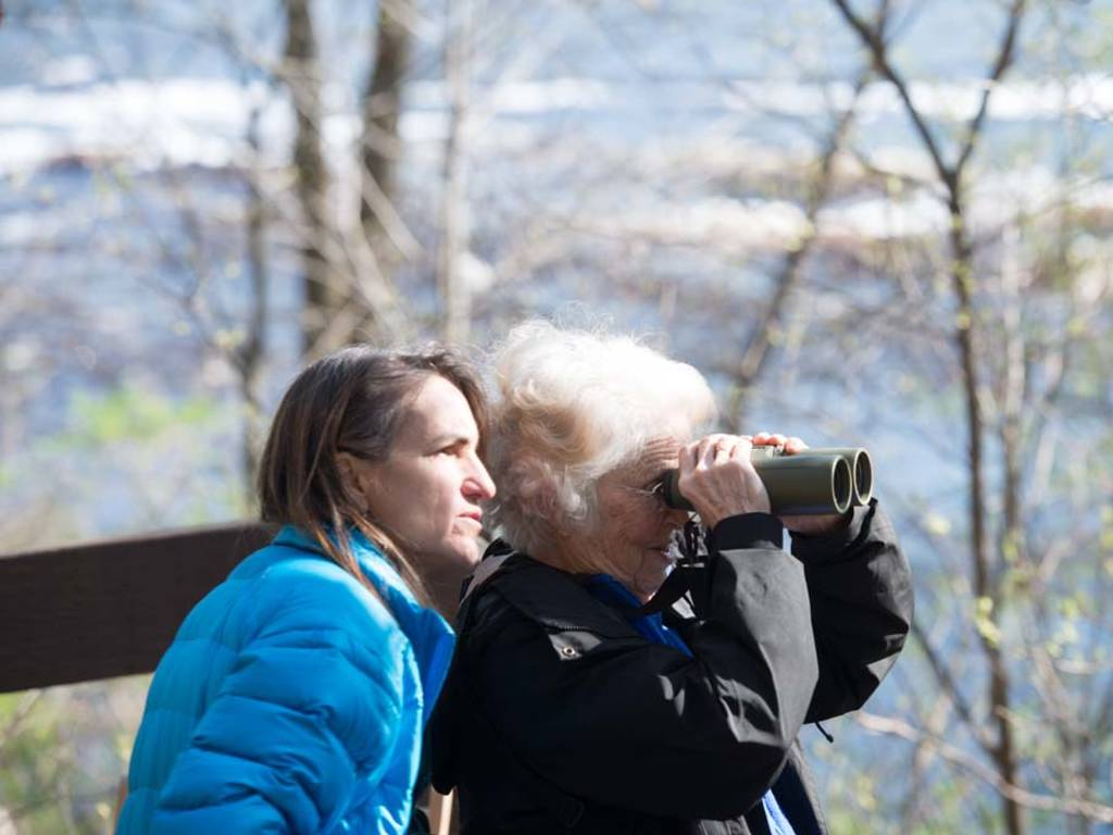Two women looking through binoculars birdwatching.