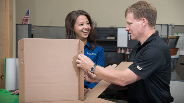 Woman and man working together to fold box