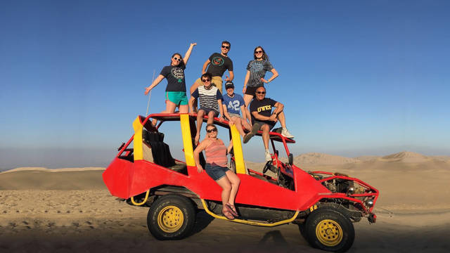 Educaiton students atop a dune buggy in Peru