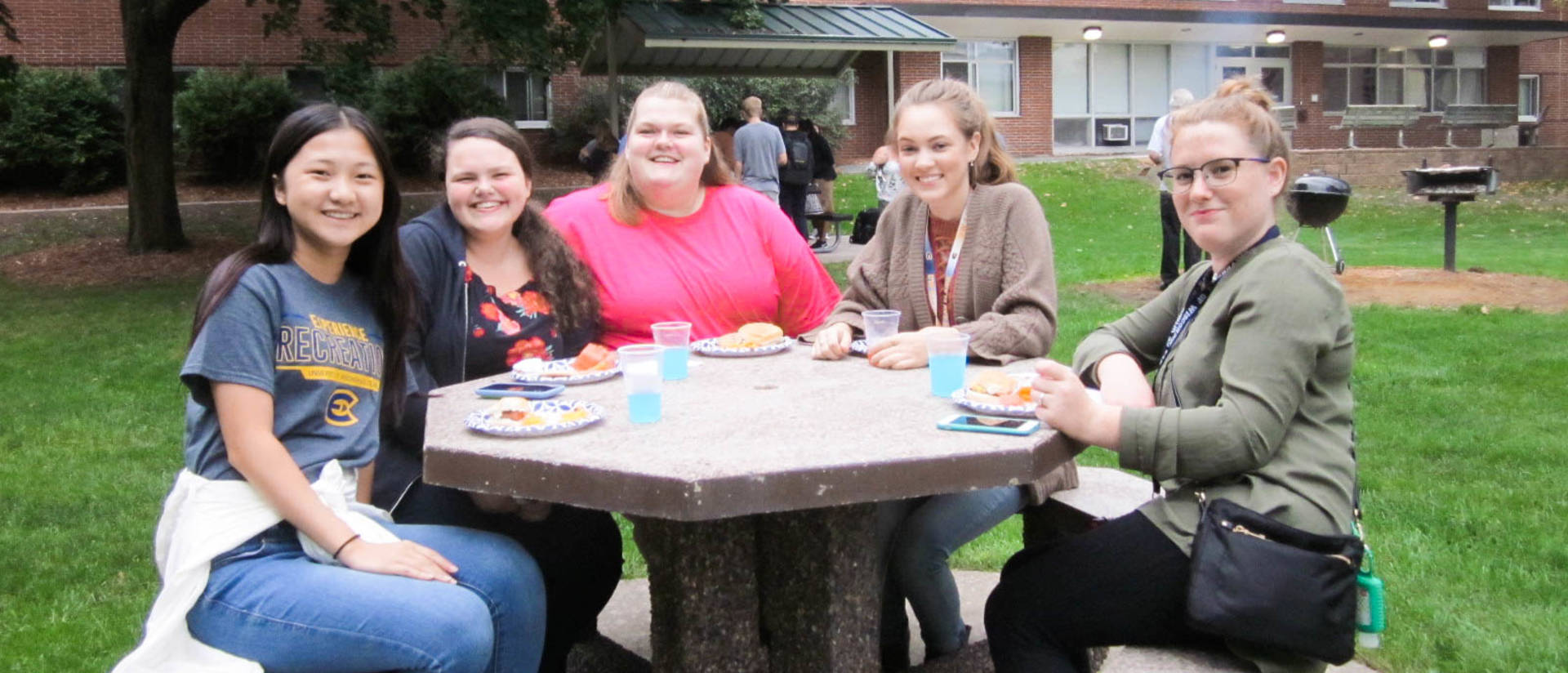 Group of four females smile at a picnic table