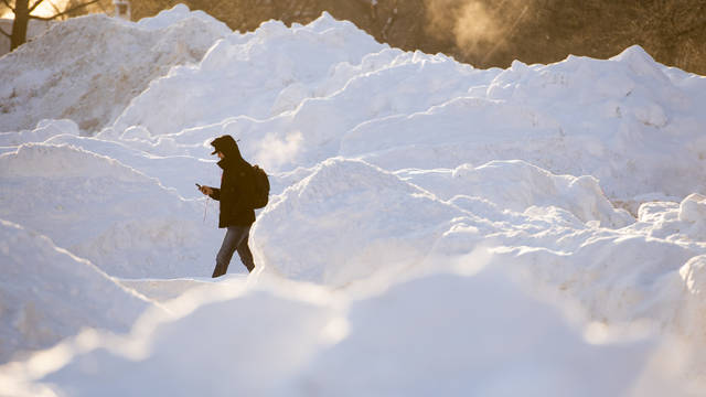 Snow piles and a lone students walking in a sea of white