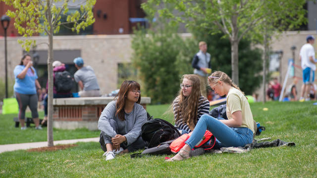 UWEC students study in campus mall on a spring day.