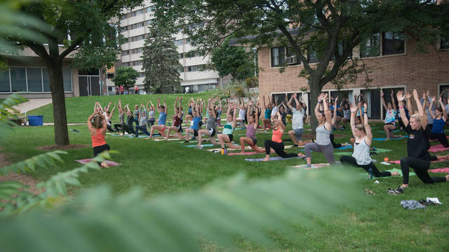 Outdoor yoga class behind Katherine Thomas residence hall