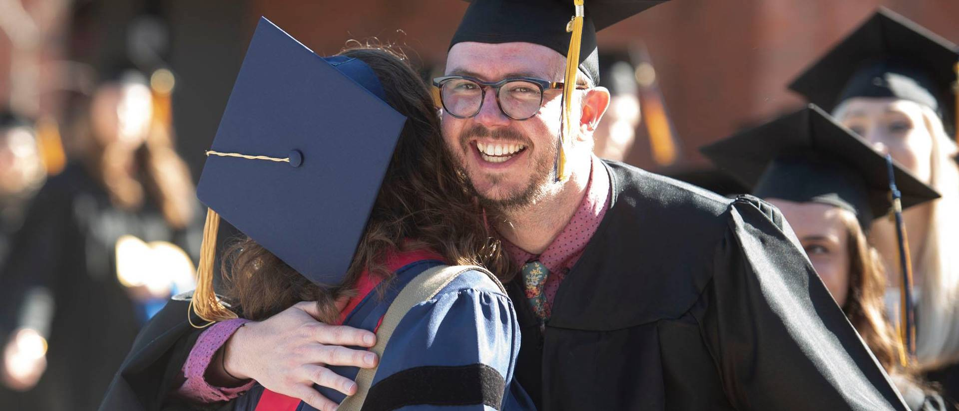 Grads hugging at commencement