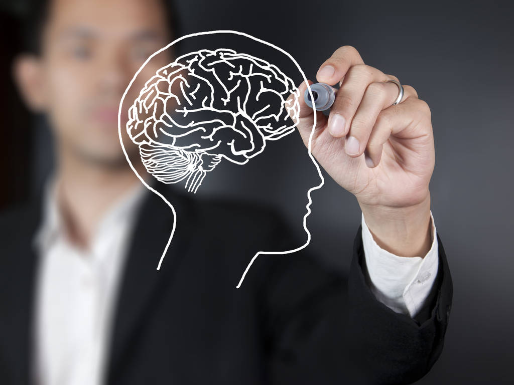 Blurred person drawing a brain on clear board with a white marker