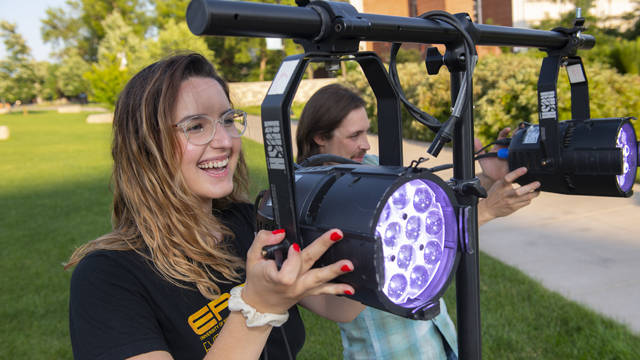Maria Derrider operating stage lighting for campus mall concert