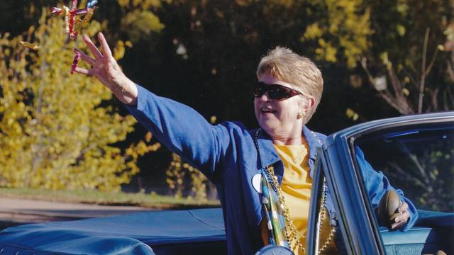 Vicki Lord Larson riding in a homecoming float vehicle throwing candy to passerby