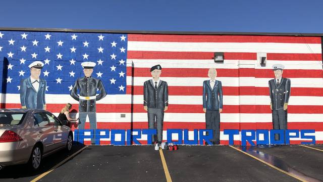 Payton Sullivan touching up Military Mural.