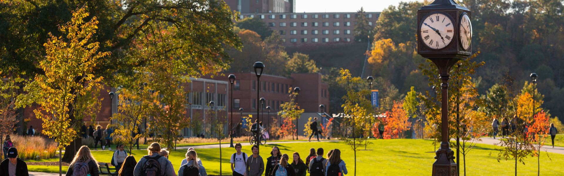 Students by clock tower in fall
