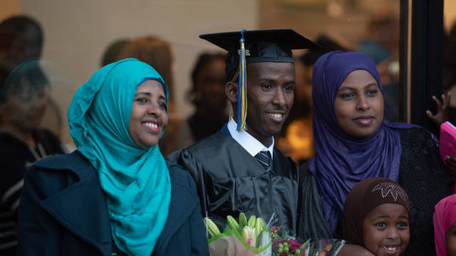 Student wearing graduation cap and gown and posing for photo with family