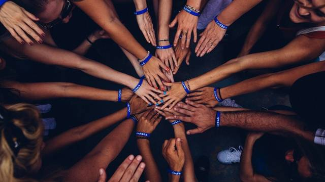 Diverse group of people in a circular huddle with their hands placed on top of one another in the center of the huddle.