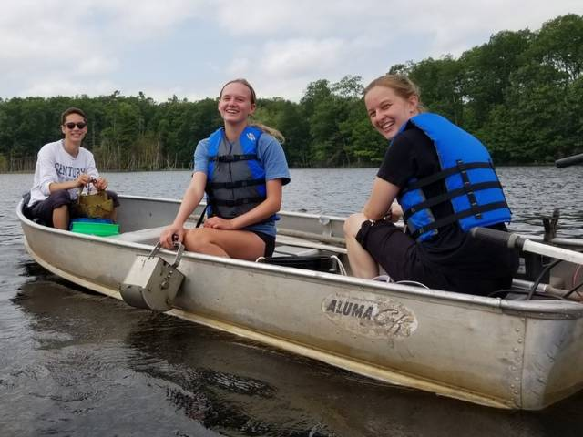 Biology students in canoe collecting moss samples.