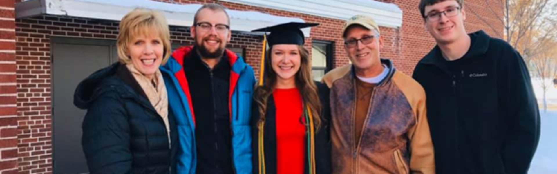 Graduate, Liz Sproul Wearing her Excellence in Sustainability Honors cord with her family