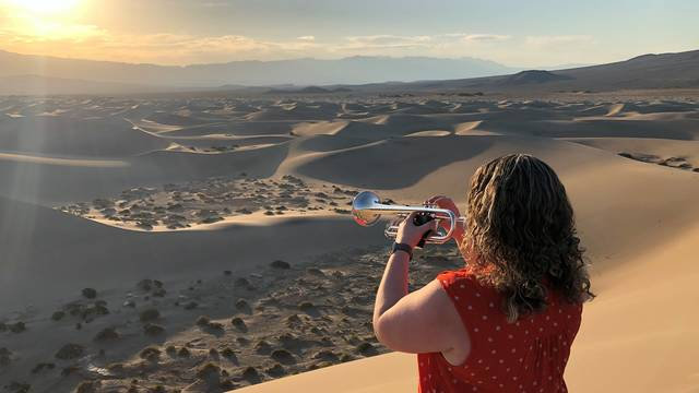 Woman plays trumpet in desert.