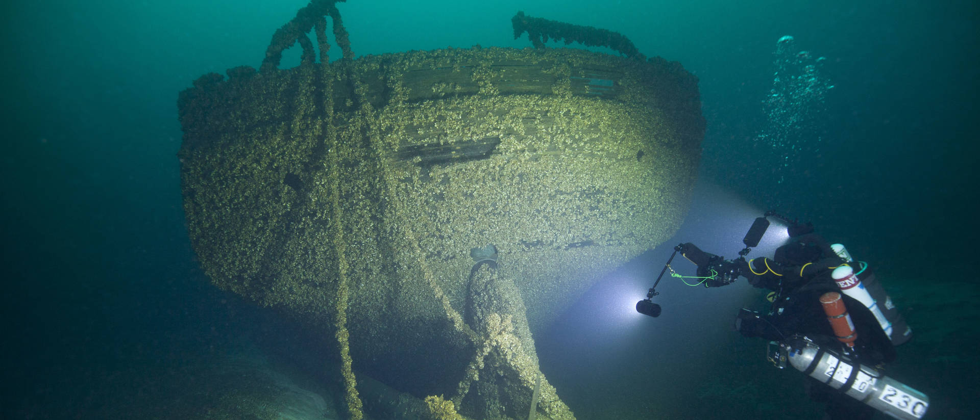 In this Aug. 24, 2019, photo provided by John Janzen, diver John Scoles maneuvers around the wreckage of the schooners Peshtigo and St. Andrews, lost in 1878 near Beaver Island in northern Lake Michigan. (Photo credit: John Janzen via AP)