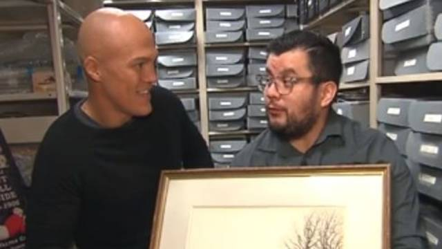 CNN host on the right, Jeremy Swick on the left holding a large framed drawing of the first football game