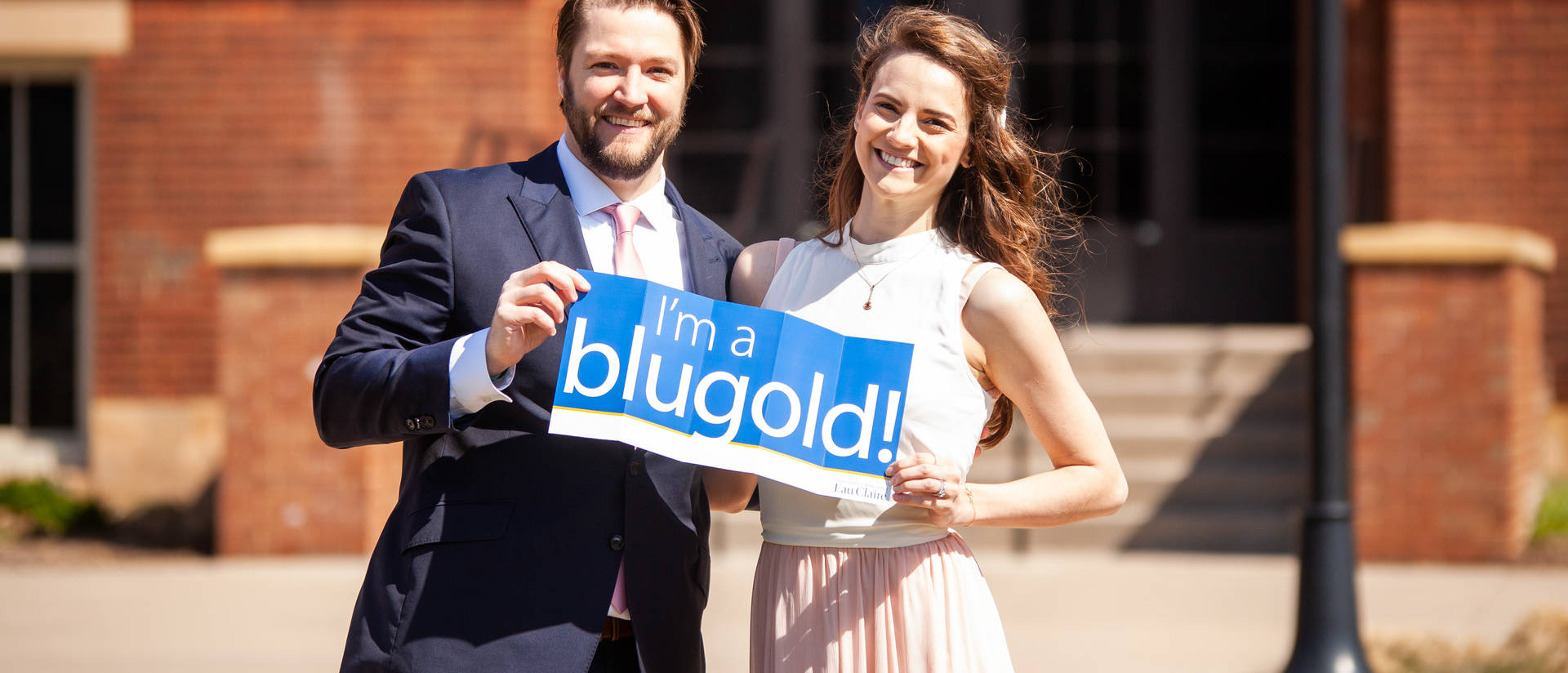 "Ryan Moertel, '12 and Jena Weiler, '13 holding up an ""I'm a Blugold"" sign after their campus wedding ceremony"