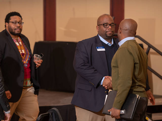 Dr. Warren Anderson at 202 Harambee event greeting attendees