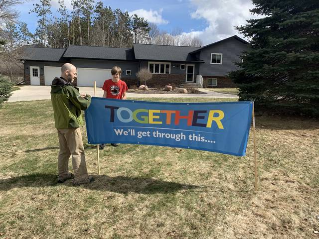 James Kiffmeyer (left) and Armin Kiffmeyer stake a banner in their front yard that reads