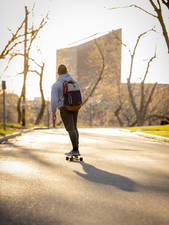 Skateboarder in the sunrise on campus.
