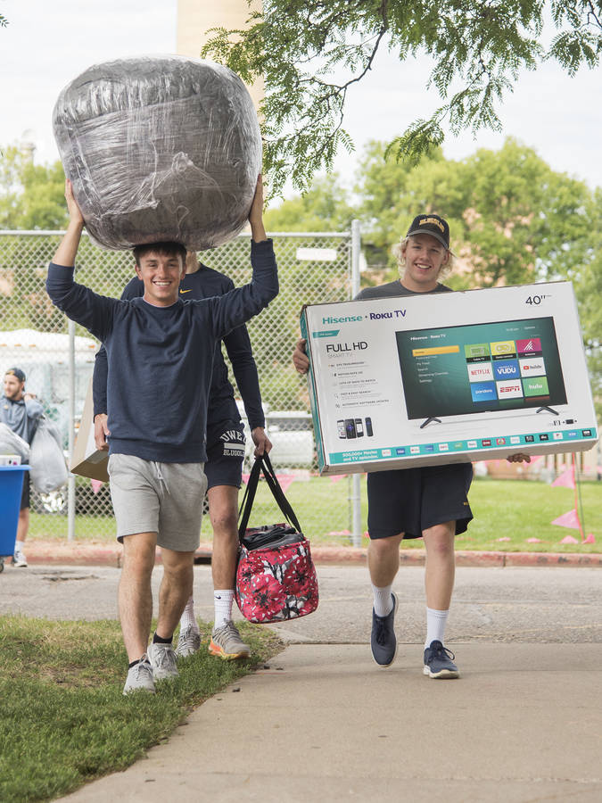 Move-in day in residence halls, students carrying loads of belongings