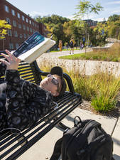 A student reading on a bench on a sunny day.