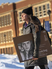 Student carrying poster across campus outside in winter
