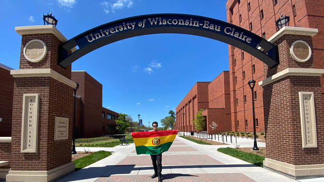 Alejandro Lama in the campus archway holding Bolivian flag.