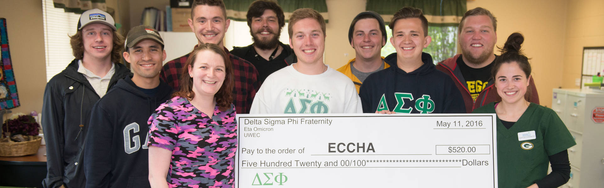 Greek Life presenting community organization with a check