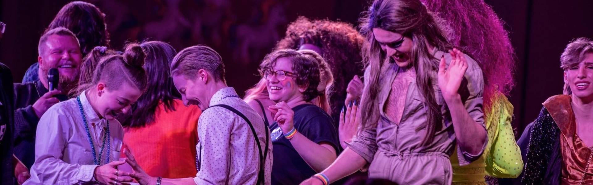 Close-up of LGBTQ+ students dancing and smiling on a large stage.