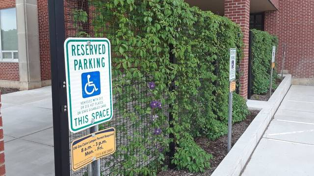 Picture of the ADA Parking spaces outside the library. A reserved parking sign is in the foreground, and a large trellis with a climbing plant is behind it