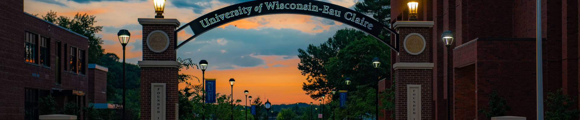 An evening picture of the UW-Eau Claire entrance gate with arch.