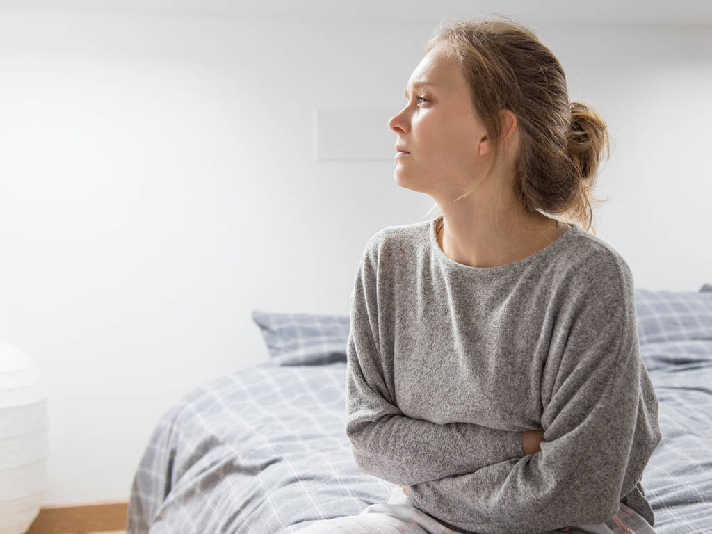 woman sitting on a bed with her arms around herself