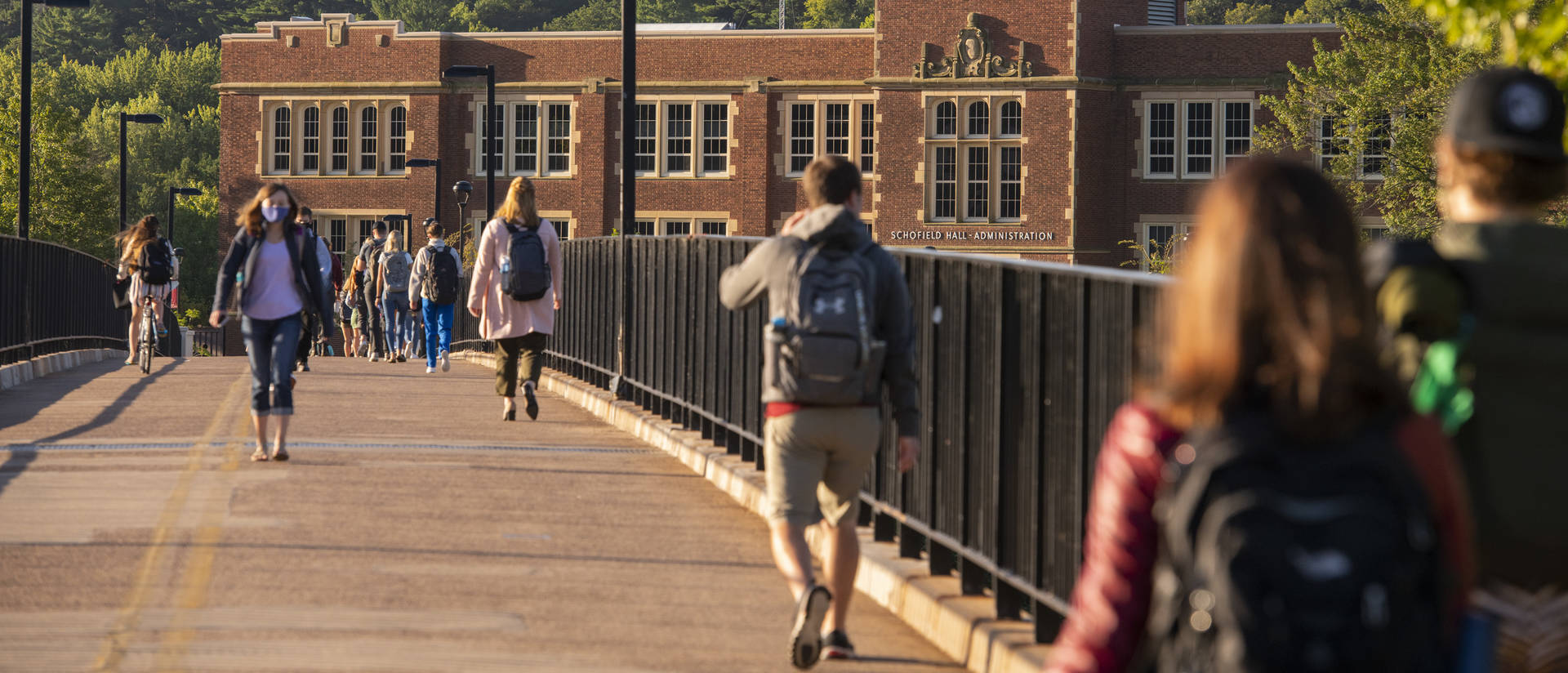 Students walk across footbridge in masks during first day of fall 2020 semester.