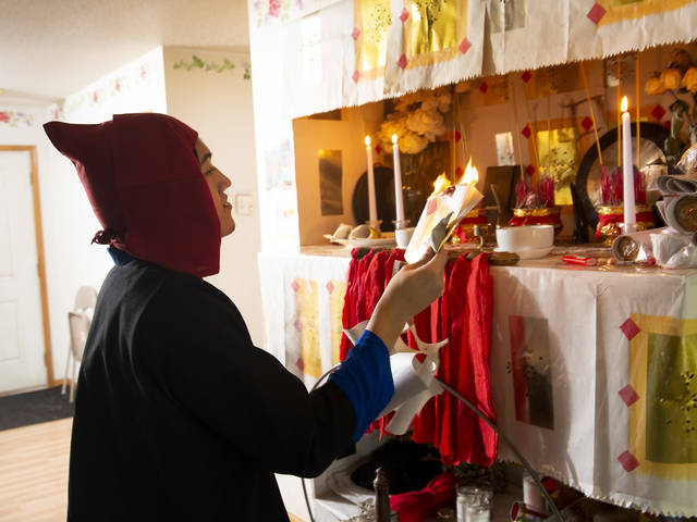 "Tou Ger ""Billy"" Lor performs a healing ceremony in front of an altar as he serves the Hmong community in his role as a shaman."